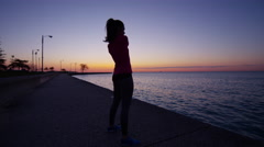 Hispanic Caucasian female silhouette fitness stretching at sunset in Chicago Stock Footage