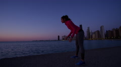 Hispanic Caucasian female silhouette stretching at sunrise after health training Stock Footage