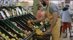 4K Cheerful worker in grocery store juggling oranges Stock Footage