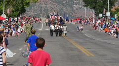 Color guard marches flag excited children watch start of parade Stock Footage
