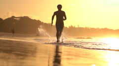 SLOW MOTION: Young sportsman running in shallow water on beautiful sandy beach Stock Footage