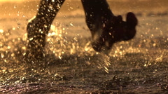 MACRO: Young athlete man running in shallow ocean, water drops sprinkling around Stock Footage