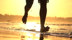 CLOSE UP: Young athleteman running in shallow ocean water at golden sunset Stock Footage