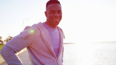 Ethnic African American male in sun flare stretching and relaxed in Chicago Stock Footage