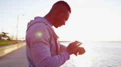 Ethnic African American male in sun flare for exercise workout with smart watch Stock Footage