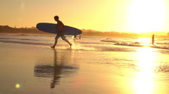 SLOW MOTION: Excited young surfer running with longboard in his hands out of sea - stock footage