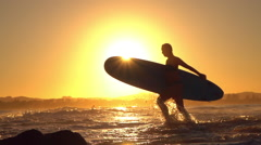 SLOW MOTION: Young surfer girl coming from surfing adventure with surfboard Stock Footage