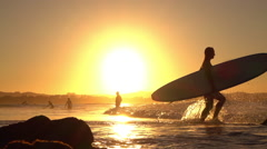 SLOW MOTION: Adventurous young surfer girl running into ocean with surfboard - stock footage