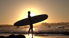 SLOW MOTION: Young female surfer holding surfboard, pointing into beautiful sea - stock footage