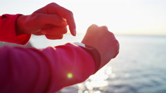 Hispanic Caucasian female wrist in sun flare with smart watch for training Stock Footage
