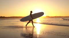 SLOW MOTION: Young surfer girl running into ocean splashing water at sunset - stock footage