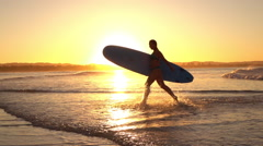 SLOW MOTION: Excited surfer girl running out of ocean splashing water at sunset Stock Footage