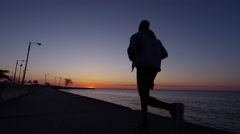 Ethnic African American male in silhouette running at sunrise by Lake Michigan Stock Footage