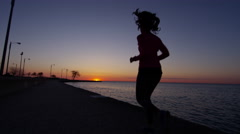 Hispanic Caucasian female silhouette at sunrise running in Chicago for wellbeing Stock Footage