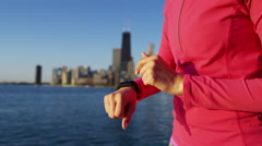 Hispanic Caucasian female outdoors in Chicago city adjusting wrist smart watch Stock Footage