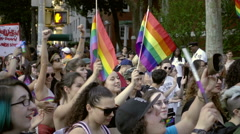 Gay women marching in LGBT Parade with rainbow flags in NYC Stock Footage