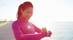 Portrait of Hispanic Caucasian female in sun flare with smart watch stretching Stock Footage