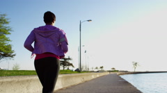 African American female doing shoreline cardio running workout with smart phone Stock Footage