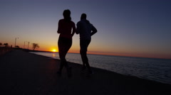 Silhouette of Multi Ethnic male and female at sunset by Lake Michigan running Stock Footage