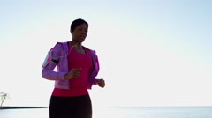 African American female in sun flare for cardio running workout with smart phone Stock Footage