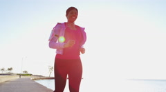 Relaxed Ethnic African American female in sun flare running with smart phone Stock Footage