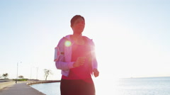 African American female in sun flare doing running workout with smart phone Stock Footage