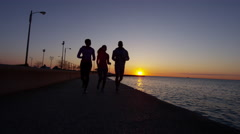 Multi Ethnic male and females in silhouette at sunrise by Lake Michigan running Stock Footage