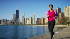 Ethnic African American female in the city doing a running workout with ear buds Stock Footage