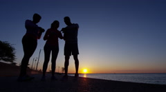 Multi Ethnic male and females in silhouette at sunset by Lake Michigan running Stock Footage