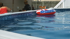 An american red white and blue styled float in a pool during summer Stock Footage