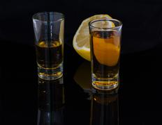 Two shots of alcohol and half of a lemon on the dark background Kuvituskuvat