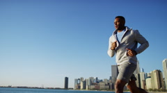 Ethnic African American male doing running activity to stay fit in the city Stock Footage