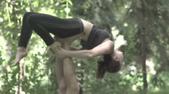 Girl doing yoga with a guy who holds her in the air. Slow motion Stock Footage