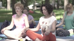 Women doing yoga in the Park day. Meditate in the Lotus position . Slow motion Stock Footage
