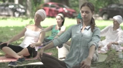 Girl does yoga in Park, sitting in the Lotus position . Slow motion Stock Footage