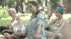 A group of girls do yoga in the park. Slow motion. Stock Footage