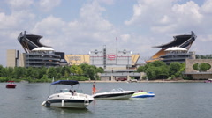 View of Heinz field from the water in the summer with people on a boats Stock Footage