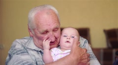 Happy grandfather holds a baby on hands and talking,play Stock Footage
