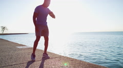 Ethnic African American male in sun flare doing cardio sport running exercise Stock Footage