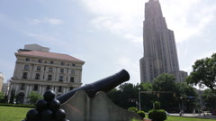 Panning up and down from the Cathedral of Learning to a cannon in Pittsburgh Stock Footage
