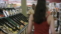 4K Worker stocking shelves in grocery store while customers shop Stock Footage