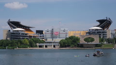 View of Heinz field from the water in the summer with people on a boat Stock Footage