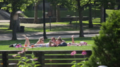 College girls sunbathing in the park during the summer Stock Footage