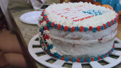 Putting icing on a red white and blue cake - stock footage
