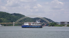 Steamboat and speedboat passing in front of a yellow bridge in Pittsburgh Stock Footage