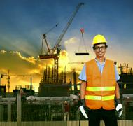 Asian construction site worker smiling face and building construction site ba Stock Photos