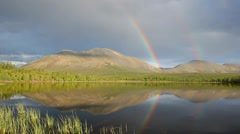 Double rainbow over lake and mountains Stock Footage