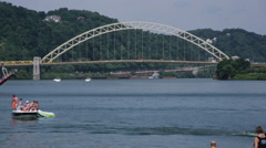 Steamboat passing in front of a yellow bridge in Pittsburgh Stock Footage
