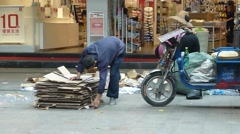 Junkmen in picking up waste paper scraps in the street. Stock Footage