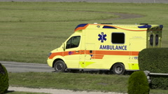 An ambulance parked on a lawn and a horse passes by at a horse race Stock Footage